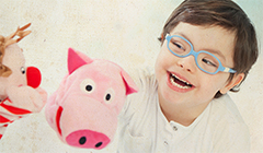 Child with blue glasses and hand puppets